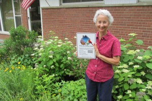 Fran Glass stands in her yard of native plants with a sign proclaiming her Bring Conservation Home Platinum certification - the highest level.
