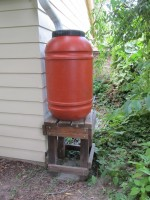A rain barrel on a stand increases the water flow
