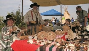Vendors dressed in Pioneer-era clothes at a booth on Prairie Day