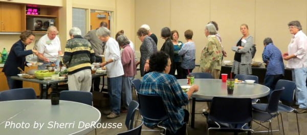 Attendees queueing for food sampling at the annual potluck and seed exchange