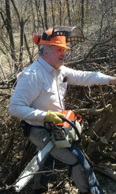 Bill Hoss with a chainsaw and bush honeysuckle
