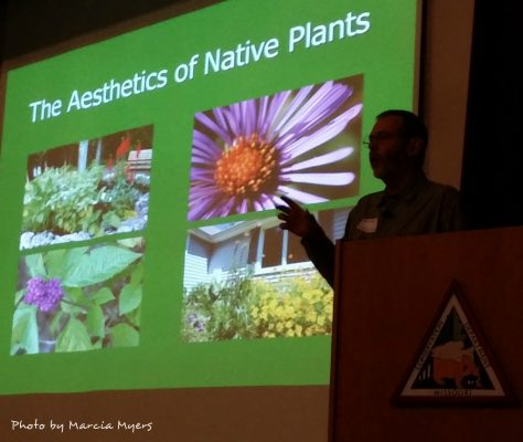 Man standing behind podium and in front of a native plant slide