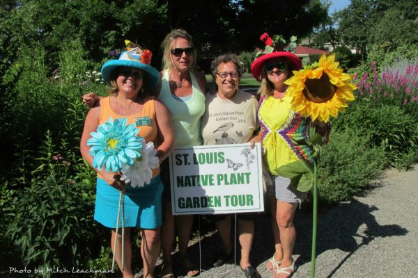 Four women with St. Louis Native Plant Garden Tour Sign