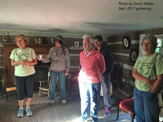 Five people standing inside log house